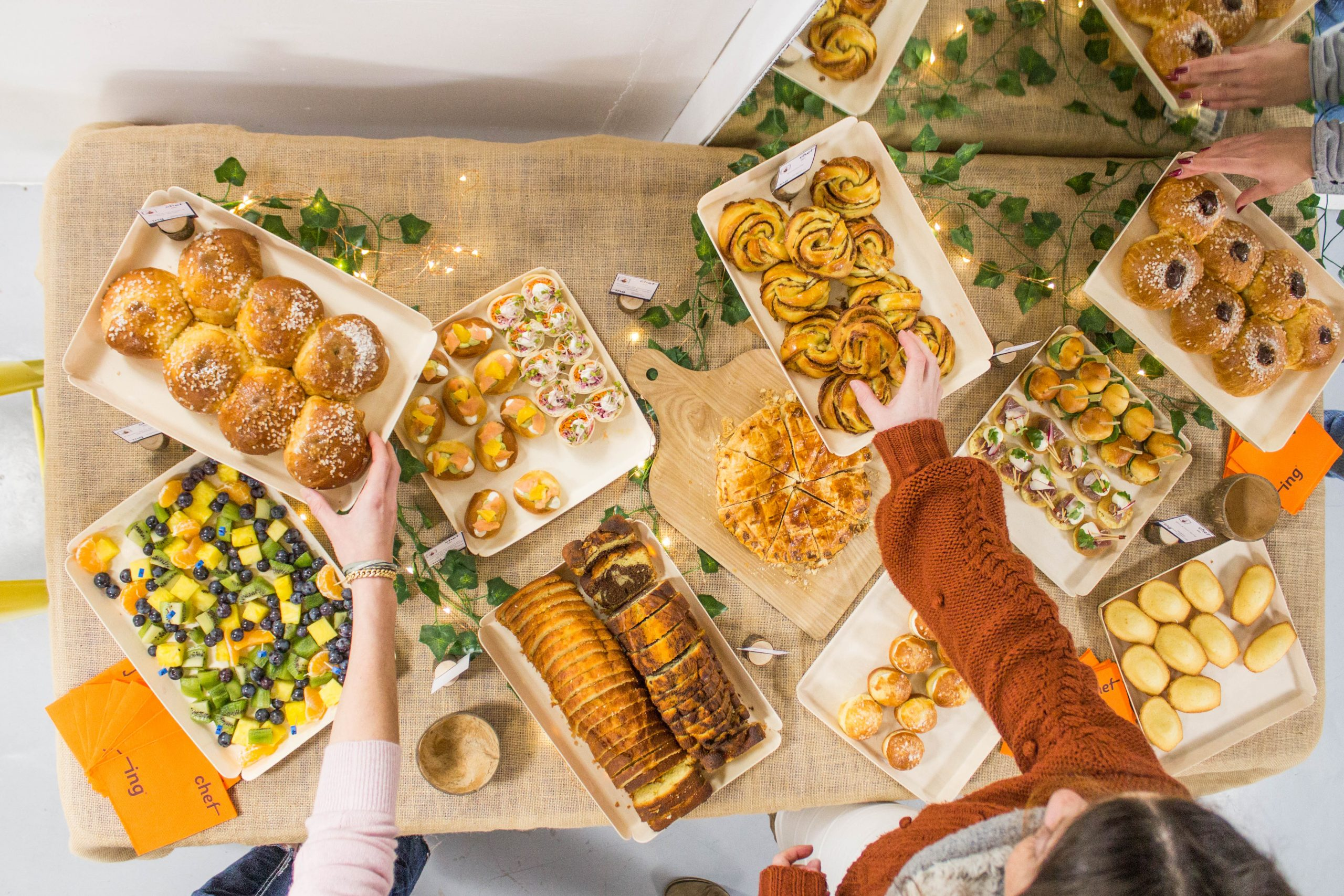 buffet petit dejeuner avec trois mains qui attrapent de la brioche et des cinnamon rolls chez chefing
