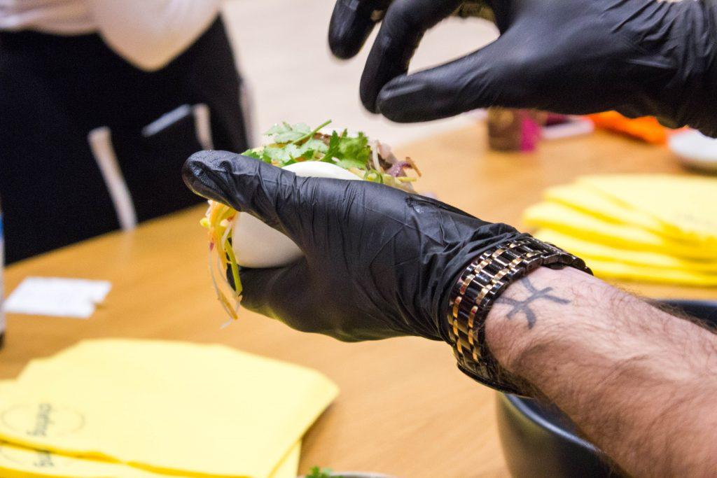 des mains d'homme avec des gants noirs tiennent un bao